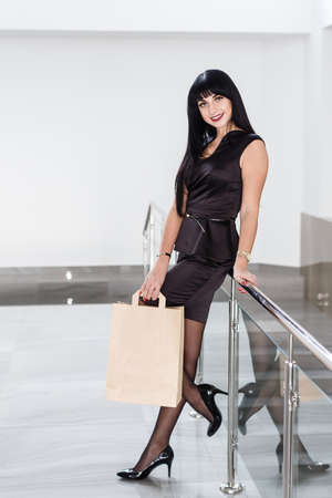 Young Beautiful smiling brunette woman dressed in a black business suit holding paper shopping bag, walking on a mall. Looking at camera.