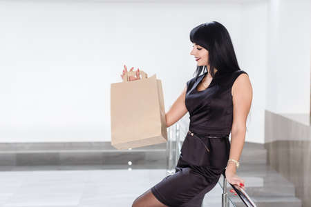 Young Pretty smiling brunette woman dressed in a black business suit holding paper shopping bag, walking on a mall. Looking to Bag. 写真素材