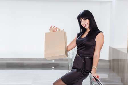 Young Pretty smiling brunette woman dressed in a black business suit holding paper shopping bag, walking on a mall. Looking at camera. Stock Photo