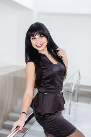 Young Attractive happy brunette woman dressed in a black business suit with a short skirt is standing against the white wall in a office leaning on railing, smiling, looking to camera.