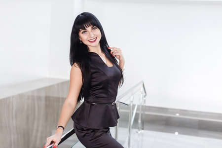 Young Pretty happy brunette woman dressed in a black business suit with a short skirt is standing against the white wall in a office leaning on railing, smiling, looking to camera. 写真素材