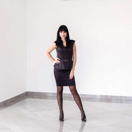 Young Attractive happy brunette woman dressed in a black business suit with a short skirt is standing against the white wall in a office, smiling, looking to camera. 写真素材