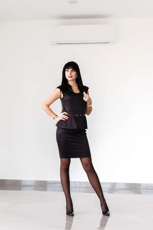 Young Attractive happy brunette woman dressed in a black business suit with a short skirt is standing against the white wall in a office, smiling. 写真素材