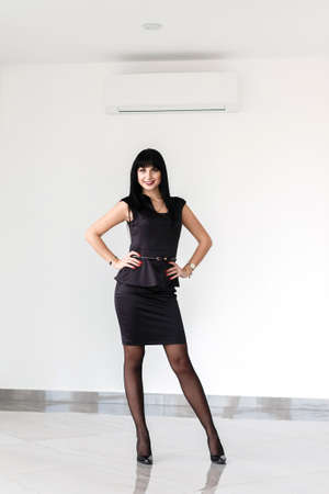 Young Beautiful happy brunette woman dressed in a black business suit with a short skirt is standing against the white wall in a office, smiling, looking to camera.