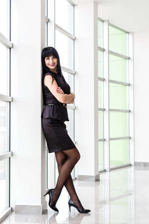 Young Beautiful happy brunette woman dressed in a black business suit with a short skirt is standing near the window in a white office, smiling, looking to camera. 写真素材