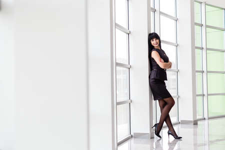 Young Attractive happy brunette woman dressed in a black business suit with a short skirt is standing near the window in a white office, smiling, looking to camera.