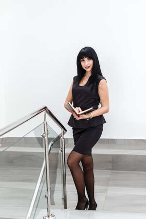 Young Attractive happy brunette woman dressed in a black business suit working with a notebook, standing in a office, smiling, looking at camera. 写真素材