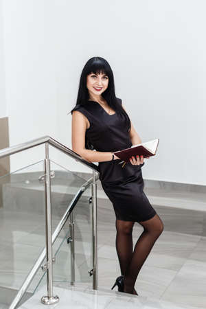 Young Beautiful happy brunette woman dressed in a black business suit working with a notebook, standing in a office, smiling, looking at camera. 写真素材