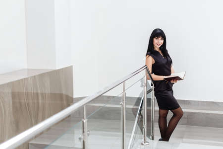 Young Beautiful happy brunette woman dressed in a black business suit working with a notebook, standing in a office, smiling.