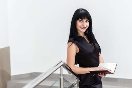 Portrait of Young Beautiful happy brunette woman dressed in a black business suit working with a notebook, standing in a office, smiling, Looking at camera.