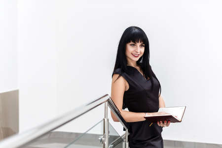 Portrait of Young Pretty happy brunette woman dressed in a black business suit working with a notebook, standing in a office, smiling.
