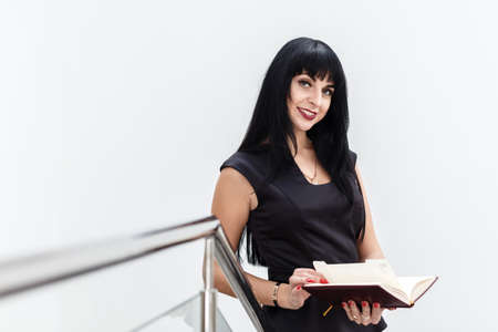 Portrait of Young Beautiful happy brunette woman dressed in a black business suit working with a notebook, standing in a office, smiling, lookinf at camera. 写真素材