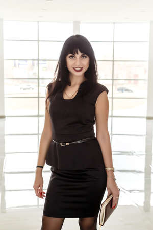 Young Attractive happy brunette woman dressed in a black business suit holding a note book, standing in a office against big window, smiling, looking at camera.