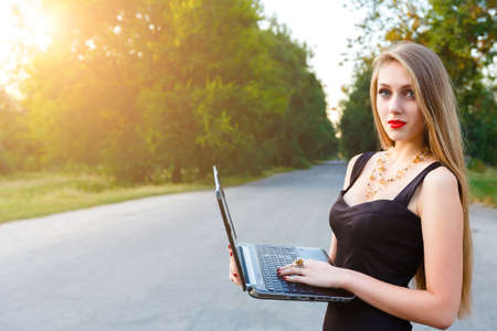 Young beautiful blonde businesswoman holding a laptop, working in a park.