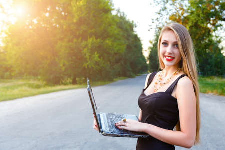 Young beautiful smiling blonde woman holding a laptop, working outdoors. 写真素材