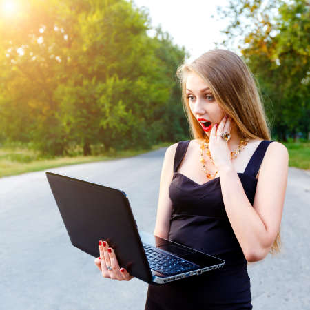 Beautiful blonde female manager with open mouth in surprise looks to laptop, working in a park outdoors on a sunset.