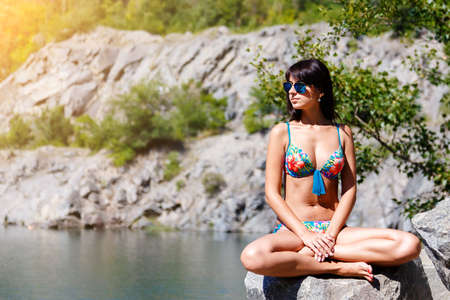 Beautiful tanned brunette girl sitting in lotus position in the mountains beach on sunny summer day