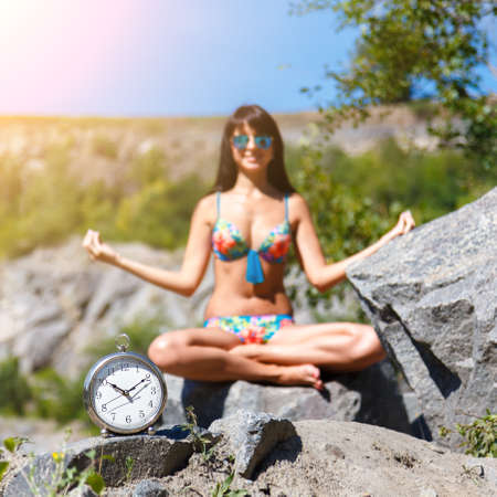 Watches and tanned sexy blurred girl sitting in the lotus position in the mountains. Concept of time to relax. Square frame 写真素材
