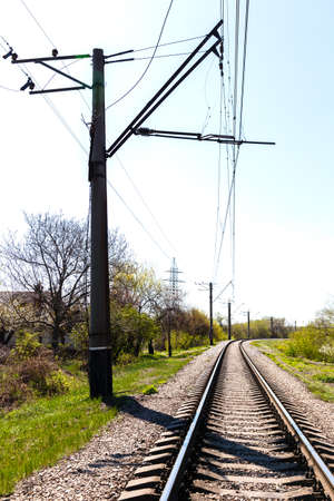 Empty Railroad Tracks with electric pole at sunny summer day.