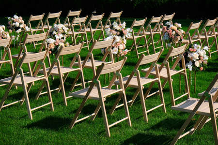 White wooden empty chairs in a row and flowers bouquets on a green grass. Wedding ceremony decorations.
