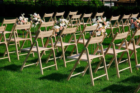 White wooden empty chairs in a row and flowers bouquets on a green grass. Wedding ceremony decorations. 写真素材 - 130715318