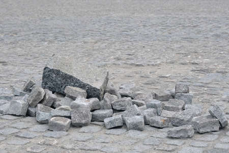 Pile of granite stones on old cobblestone pavement. 写真素材