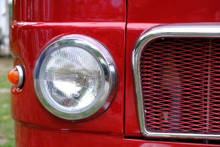 Frontlamps and radiator of old vintage red car ckose-up. 写真素材