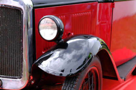 Headlight and radiator of old vintage red car ckose-up.