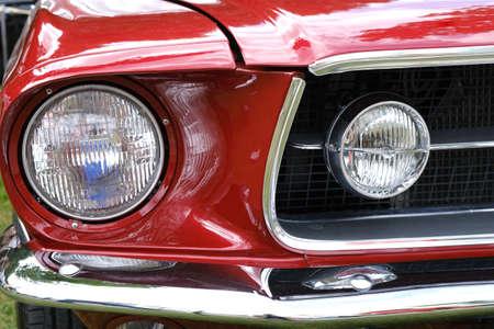 Koplampen, radiator en kap van oude retro rode auto ckose-up.