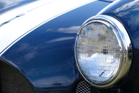 Headlight and hood of old retro blue racing car ckose-up.