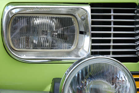 Frontlamps and radiator of old vintage retro green car ckose-up.