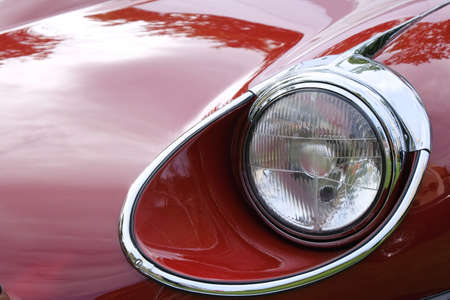 Headlight and hood of old retro red racing car ckose-up.