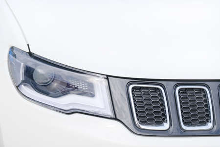 Headlight and radiator of modern white suv car ckose-up. 写真素材
