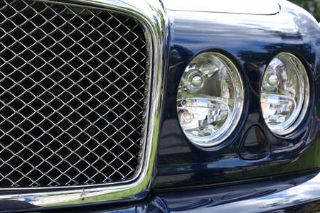 Headlights and radiator of luxury retro vintge blue car ckose-up. 写真素材 - 130716591