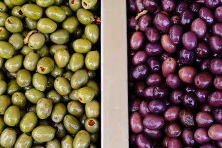 Two types of marinated olives for sale in a market window. Mediterranean delicacies, dietary healthy food. Top View.
