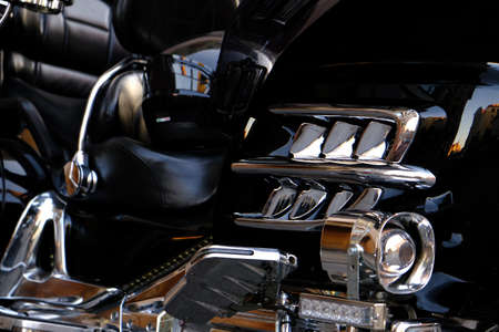 Engine chrome parts of a black Luxury motorcycle close-up.