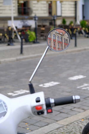 Urban white scooter is parked on cobblestone road in a tourist center of the city. Handle controls, mirror with reflection of an old building close-up. Focus on a mirror.