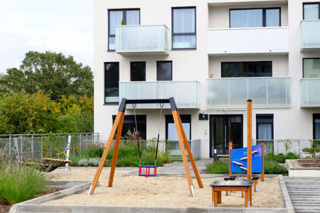 Playground with a hammock and swing in a cozy courtyard of modern residential district.