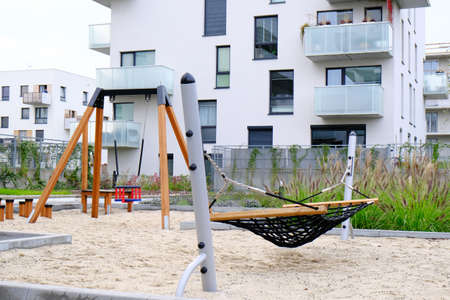 Hammock and swing on a children playground in a cozy courtyard of modern residential district.