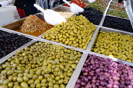 Various marinated olives for sale in a market window. Mediterranean delicacies, dietary healthy food. Фото со стока