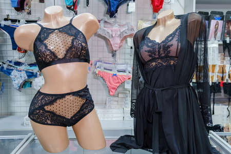Two mannequins dressed in beautiful black lace women's underwear in a lingerie store window.