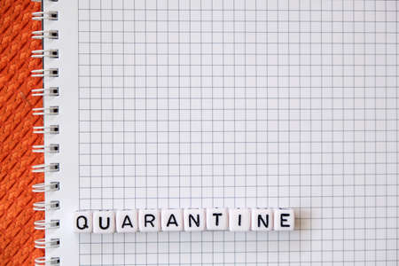 Text Quarantine , word made of cubic letters on a white paper note pad background. Working home at coronavirus pandemia concept