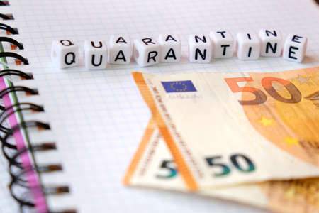 Text Quarantine , word made of cubic letters and 50 Euro banknotes on a white paper copybook background. Quarantine coronavirus concept