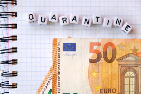Text Quarantine , word made of cubic letters and 50 Euro banknotes on a white paper copybook background.