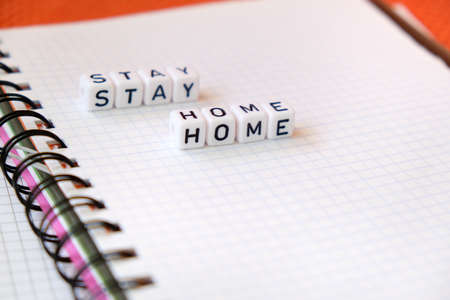 Text Stay Home , word made of cubic letters on a white paper note pad background. Quarantine coronavirus concept