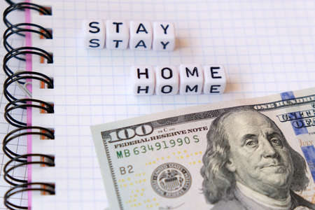Text Stay Home , word made of cubic letters and american money dollars on a white paper copybook background. Quarantine coronavirus concept Stock Photo