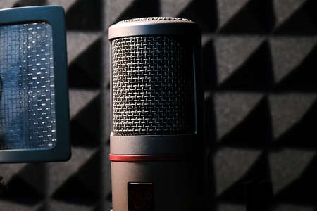 Professional Microphone In a Dark Studio with Sound Absorbing For Audio Recording Stock Photo