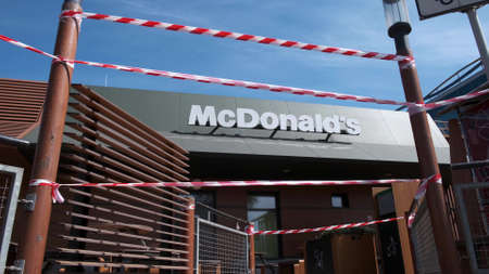 KRYVYI RIH, UKRAINE - APRIL, 2020. McDonald's fast food restaurant building surrounded by red and white warning tape, quarantined due to the Covid 19 coronavirus pandemic