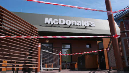 KRYVYI RIH, UKRAINE - APRIL, 2020. Building of McDonald's fast food restaurant surrounded by red-white warning tape. Quarantine of Covid-19 coronavirus pandemia Editorial