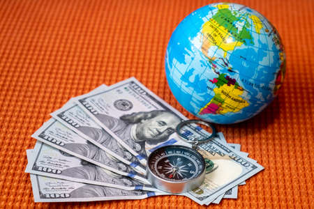 Five Hundred Dollars USA, Compass, Globe of Planet Earth on a Fabric Texture  Background Closeup. Travel, tourism, adventures Concept.